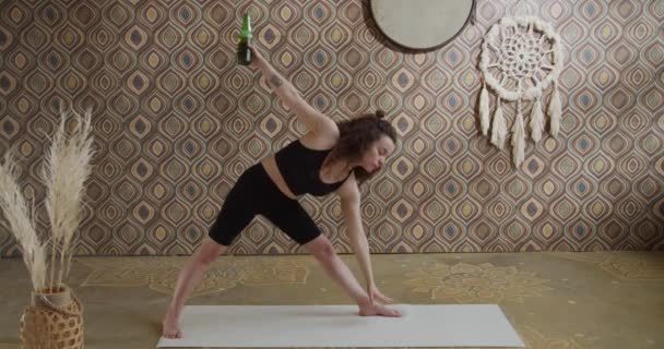Pivní jóga. Kudrnatá mladá žena, která cvičí jógu s lahví piva. Sporty štíhlé dívka dělá víno jóga v jasném, atmosférický jóga místnost v dopoledních hodinách
