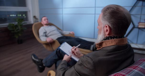 Professional gray-haired male psychologist listens to a patient and takes notes on a tablet during a psychological consultation with a depressed male patient. Psychology, mental therapy and people