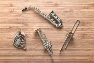Set of golden toy brass wind orchestra instruments: saxophone, trumpet, french horn and trombone. Music concept.