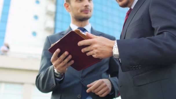 businessmen standing near office building