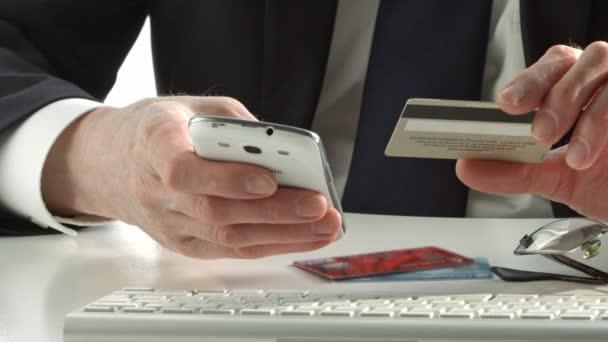 Männer halten Kreditkarte in der Hand und nutzen Smartphone für Online-Einkäufe
