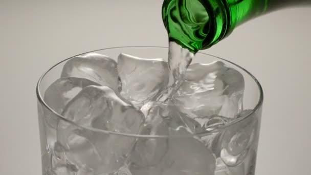 minerální voda se nalije do sklenice ze zelené láhve