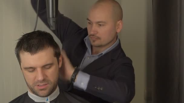 Barber makes styling hair with hair dryer and hands