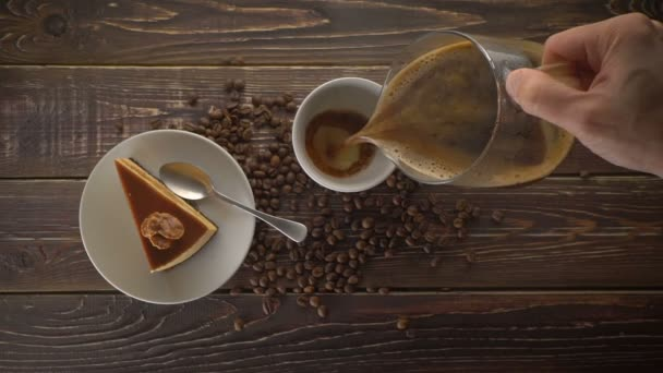 Hand pouring freshly brewed coffee to a cup on wooden table