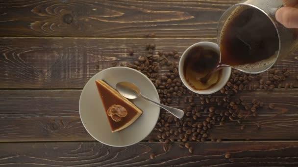 Mužské ruky čerstvě uvařenou kávu do šálku na dřevěný stůl