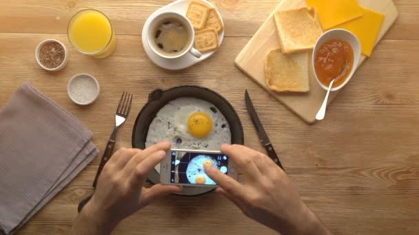 Vyfotit smažených vajíček s mobilním telefonem. Telefon v mužských rukou. Pohled shora