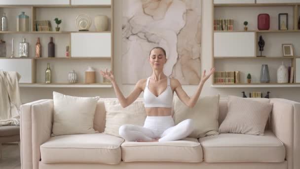 Figyelmes fiatal többnemzetiségű hölgy gyakorló meditáció otthon, nyugodt Y-generációs vonzó lány ül kanapén lótuszban póz csinál jóga egyensúly, egészségügyi ellátás, pihentető és mentális terápia koncepció
