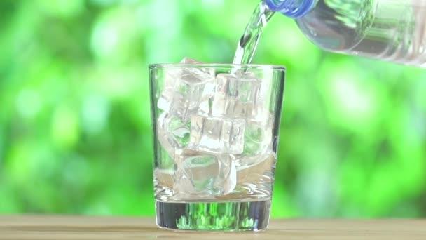 Láhev s vodou a sklenici ledové kostky