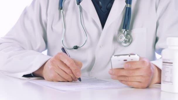 Arzt hält Smartphone in der Hand und schreibt Rezept