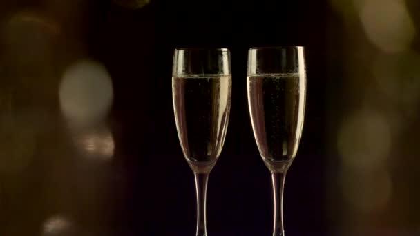 zwei Flöten mit prickelndem Champagner mit Urlaubs-Bokeh