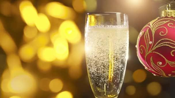 šumivé šampaňské víno v glasse a červené dekorace koule