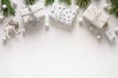 Vánoční bílé dárky, sáně, sobi, věčně zelené větve na bílém pozadí. Vánoční přání s kopírovacím prostorem. Pohled shora. Plocha.