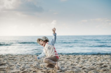 Little girl with a hat jumping and running on the beach