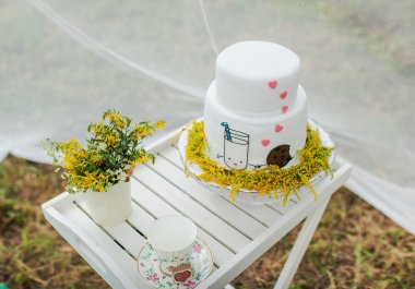 Funny wedding cake from mastic with a mug of milk and cookies.