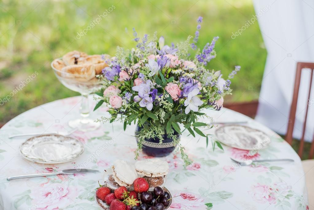 Served table outdoors. Flower arrangement with lavender and roses. Wedding decorations.