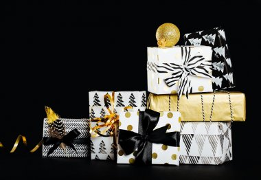 Modern painted paper black and white presents wrap with  bow on a black background