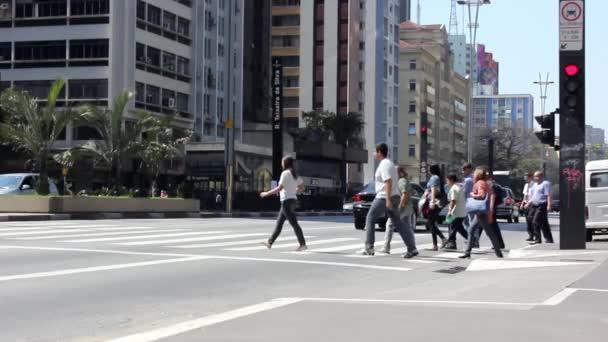 Lidé na chodníku v těsné blízkosti Paulista Avenue