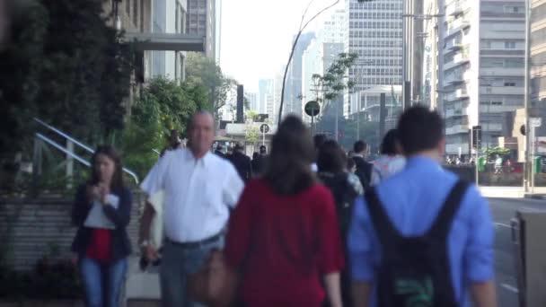 Lidí, kteří jdou v těsné blízkosti Paulista Avenue