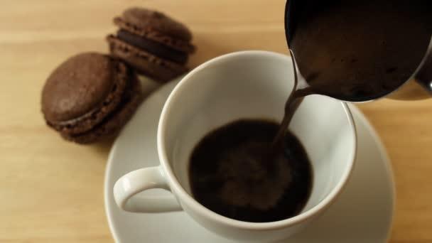 Káva se nalije do bílý šálek na dřevěný stůl s makaróny a skořicí