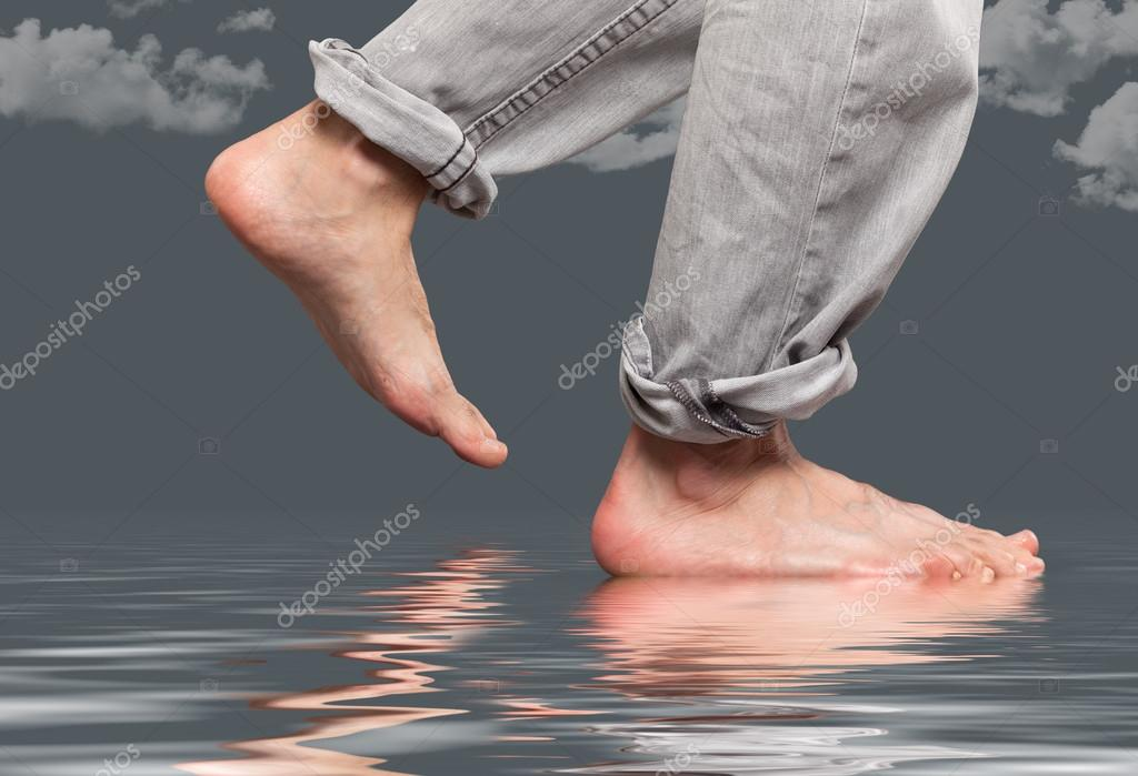 Close up of feet walking by the water
