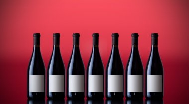 Unopened wine bottles on a red background