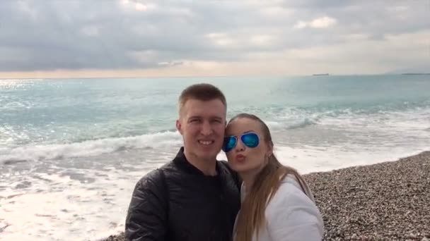 Young happy couple taking selfie  on beach using smartphone mobile cell phone camera.