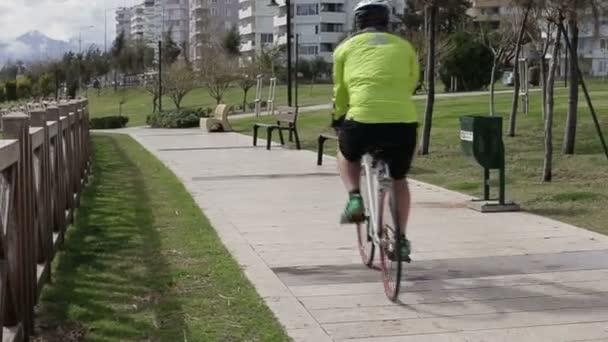 Zdravý muž na kole v parku venkovní fitness. Muži, jízda na kole, cyklista jede za slunného dne v parku