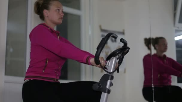 Active women in sport shoes pedaling on a stationary bike in the gym