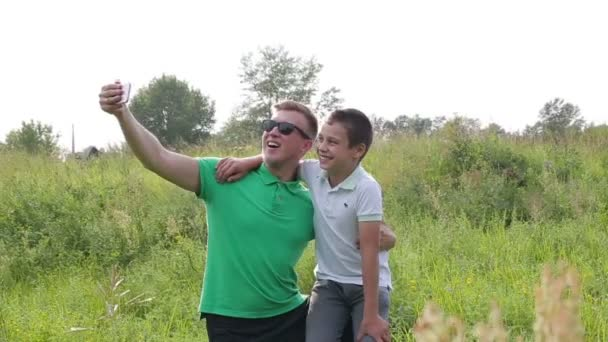 Šťastný otec a syn hraje, obrázky ze sebe používat smartphone