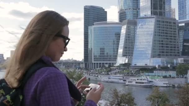 Junge Frau machen ein Foto von hoher Wolkenkratzer mit Smartphone-Handy-Kamera.