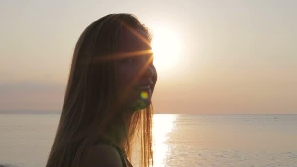 Krásná dívka se těší na moře při západu slunce