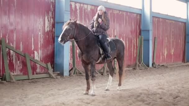 Fiatal nő lovagolni a lovat az istállóban