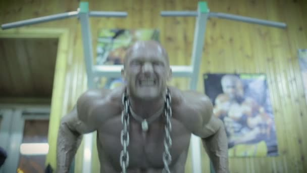 Bodybuilder doing push-ups on exercise bars in the gym.