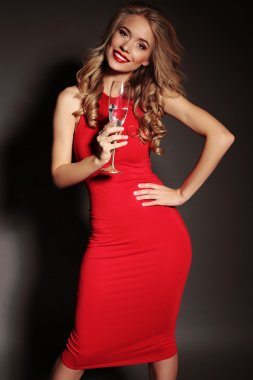 blond woman in red dress holding glass of champagne