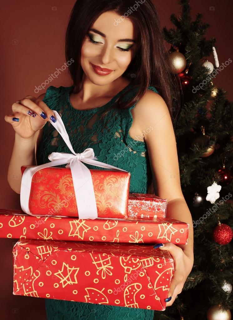 Usmívající se žena s tmavými vlasy dlouhé zelené krajkové šaty drží červené  dárkové boxy — Stock 2697b827909
