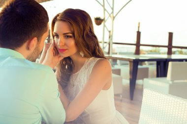 beautiful couple sitting in a restaurant and looking at each other