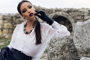 elegant brunette wears white shirt, leather skirt and gloves