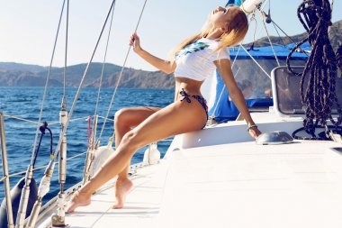 beautiful woman in swimsuit relaxing on yacht