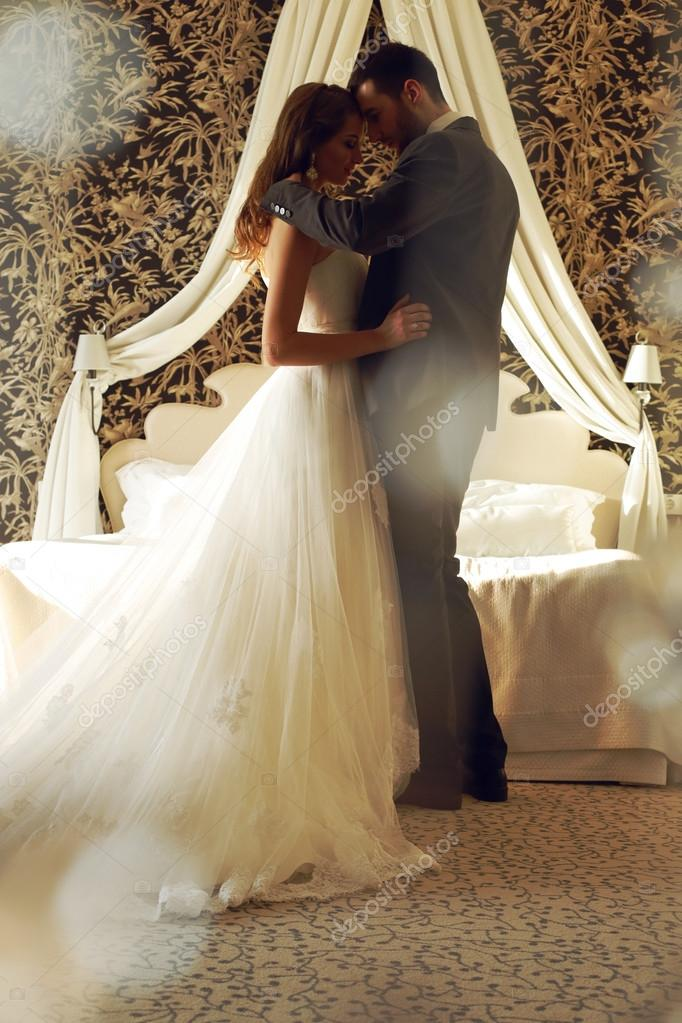 beautiful couple and bride wear wedding clothes,embracing  in bedroom
