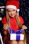 Fényképek Christmas girl in santa hat with gift