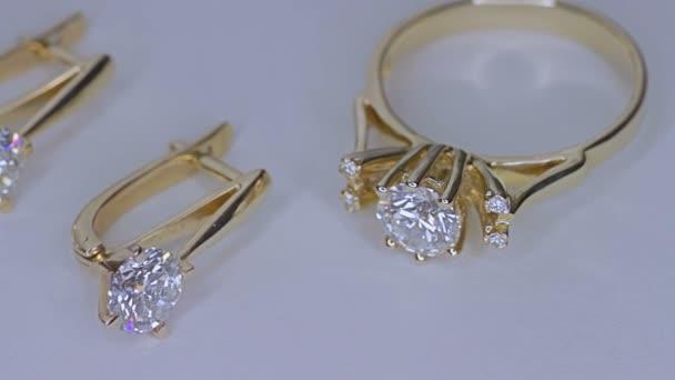Zlatý prsten s diamantem na bílém pozadí