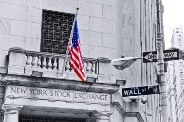 The side entrance of New York Stock Exchange and a street sign of Wall Street