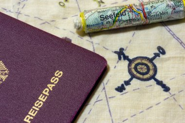German passport and rolled up map on chart