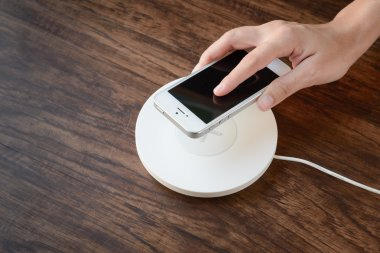 a hand putting mobile phone on a wireless charger, modern equipm