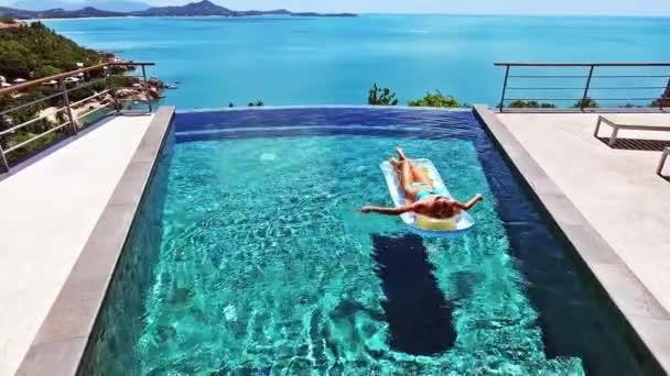 Mädchen schwimmt im Pool auf einer Luftmatratze