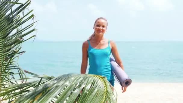 woman holding exercise mat on the beach