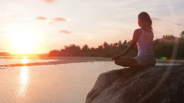 žena přemýšlí v lotus jógy na pobřeží moře na pláži