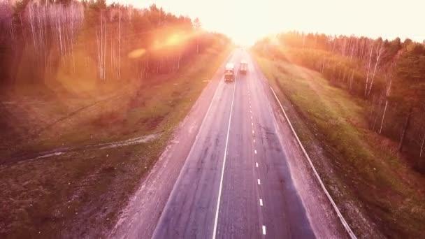 Lety nad dálniční silnici na západ slunce. Letecký pohled na nákladních automobilů na silnici.
