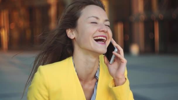 Zeitlupe. brünette junge Frau telefoniert und lacht in der Nähe von Bürogebäuden in der Großstadt.