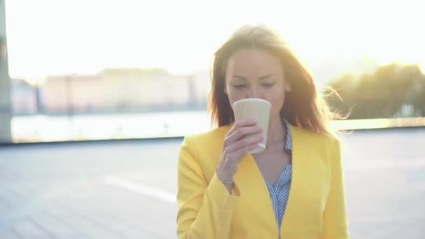 Blured background. Young beautiful girl in a yellow jacket near office walking with the coffee. Smiling business woman with cup of tea at the business center. Bright sunlight in the morning.